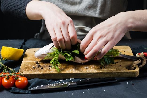 シェフの手は、パセリとコリアンダーで木のまな板にドラドの魚を詰めました。