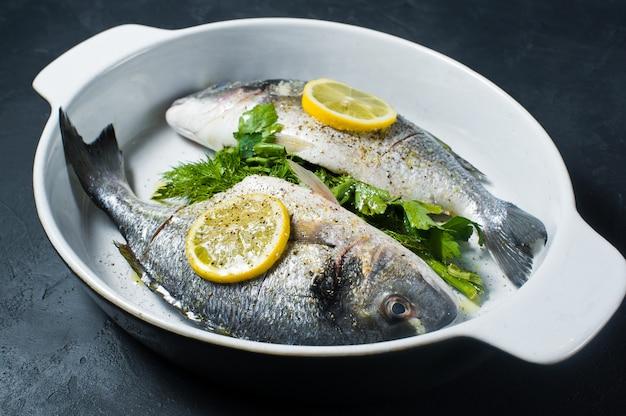 生のドラド魚のオリーブオイル、塩、コショウ、レモンのスライスの上にマリネ。