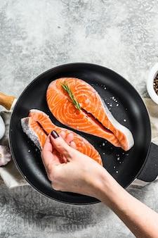 Шеф-повар солит сырой стейк из лосося в сковороде. здоровые морепродукты. вид сверху..