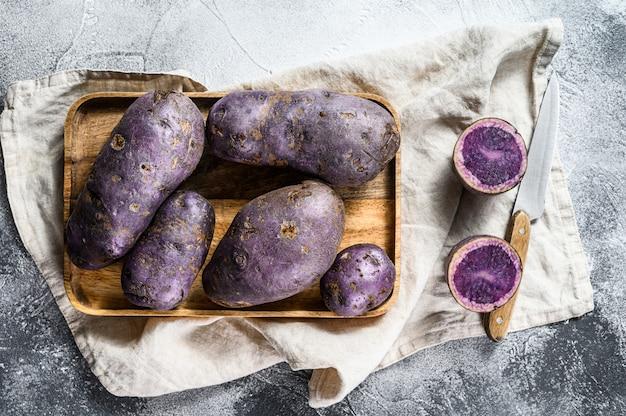 まな板の上の生の紫ジャガイモ。上面図。