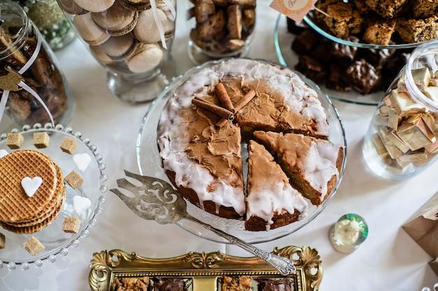 パーティーのためのデザートテーブル。オンブルケーキ、カップケーキ、甘さと花