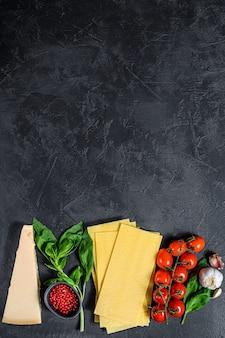 生のラザニアシート。材料バジル、チェリートマト、パルメザンチーズ、ニンニク、コショウ。黒の背景。上面図。テキスト用のスペース