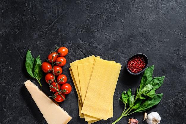 ラザニアを調理する概念。材料、ラザニアシート、バジル、チェリートマト、パルメザン、ニンニク、コショウ。黒の背景。上面図。テキスト用のスペース