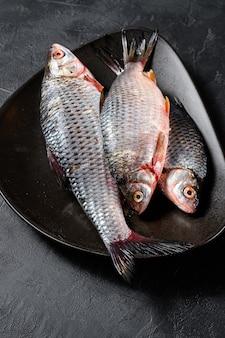 黒いプレートに生フナ。川の有機魚。黒の背景。上面図