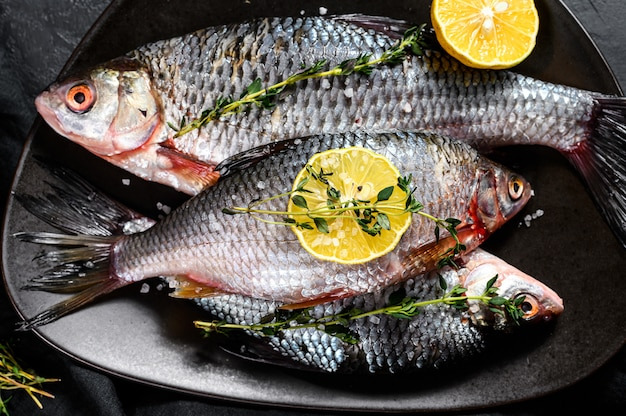 黒い皿にタイムとレモンのフナ。川の有機魚。黒の背景。上面図