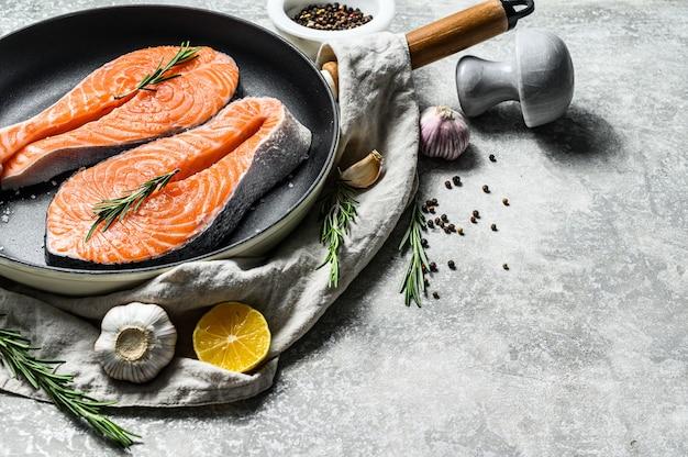 Сырой стейк из форели на сковороде. здоровые морепродукты. серый фон вид сверху. пространство для текста