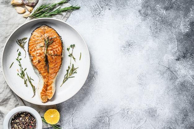 グリルサーモンステーキ。大西洋の魚。灰色の背景。上面図。テキスト用のスペース
