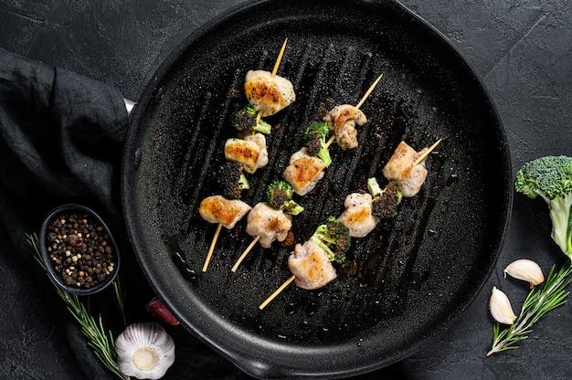 バーベキュー鶏の胸肉の串焼き。ブロッコリ。黒の背景。上面図