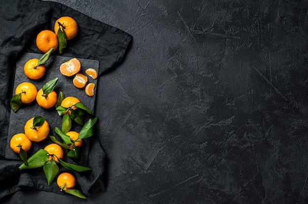 Мандарины, мандарины с листьями. черный фон. вид сверху. пространство для текста