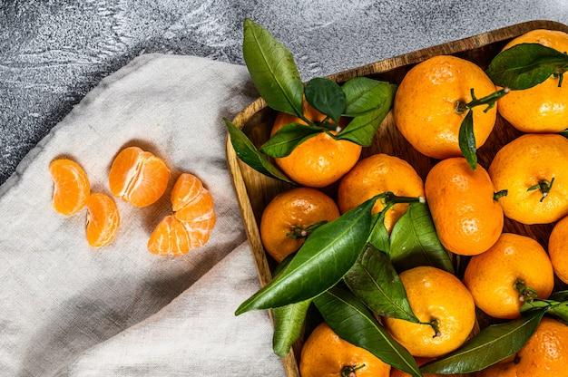 Свежие фрукты мандаринов или мандарины с листьями в деревянной миске. серый фон вид сверху