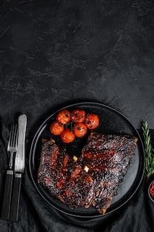 Пикантные свиные ребрышки на гриле. мясо барбекю. черный фон. вид сверху. пространство для текста