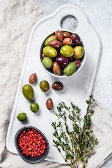 Смесь разноцветных оливок с косточкой. серый фон вид сверху