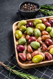 Микс из разноцветных соленых оливок с косточкой. черный фон. вид сверху