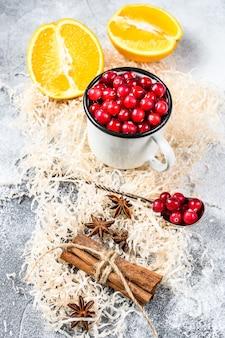 冬のベーキングクッキーの材料。ジンジャーブレッド、フルーツケーキ、ドリンク。クランベリー、オレンジ、シナモン、スパイス。クリスマス料理。灰色の背景。上面図