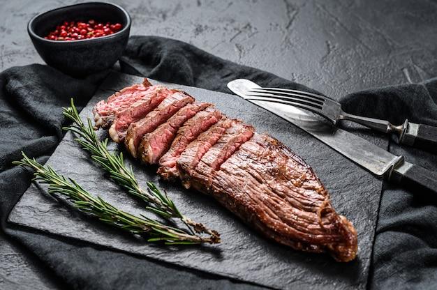 黒い石の板の上に霜降り牛肉のローストステーキ。黒の背景。上面図