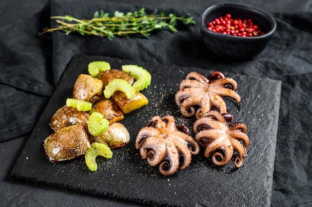 Жареный осьминог. запеченный картофель и сельдерей. черный фон. вид сверху
