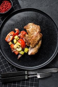 野菜と七面鳥のモモ肉のロースト。黒の背景。上面図