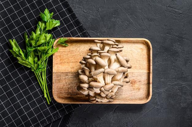 パセリと木製のボウルに生ヒラタケ。自然食品。黒の背景。上面図。テキスト用のスペース