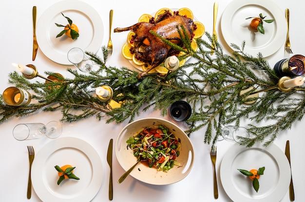 クリスマスのお祝いディナー。おいしい伝統的な休日の食事とそれらを食べる人々の手。おいしい料理が飾られたテーブル。フラットレイ。白いテーブル