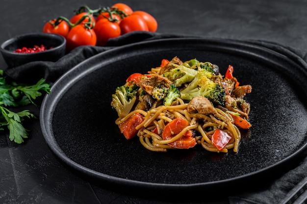 Размешайте жареную лапшу, традиционный китайский вок. палочки для еды, ингредиенты. азиатская лапша с овощами, мясом. черный вид сверху.