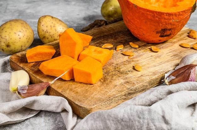 Ингредиенты для тыквенного супа. кусочки тыквы на разделочной доске. крем-суп. , вегетарианская кухня