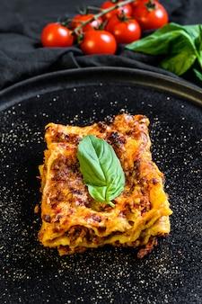 Кусочек вкусной горячей лазаньи. традиционная итальянская кухня. вид сверху
