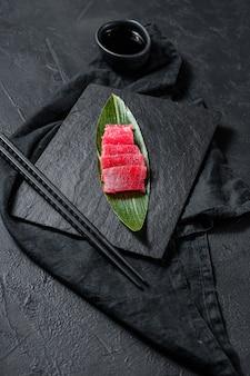 Свежий сырой тунец сасими на каменной доске. вид сверху