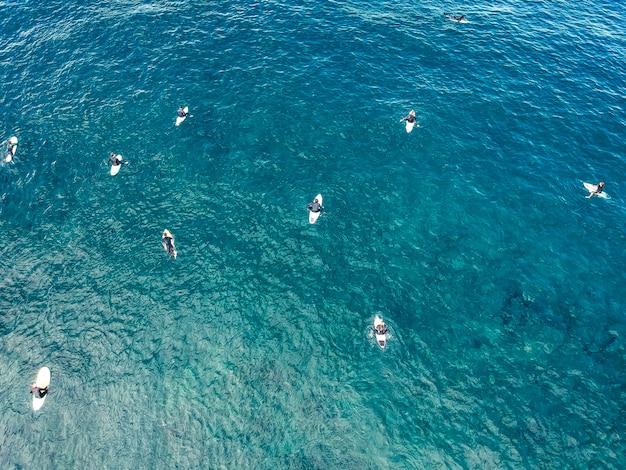 Аэрофотоснимок серферов в лазурных водах на фоне атлантического океана