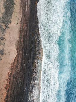 Аэрофотоснимок серферов в волнах атлантического океана. песчаный пляж