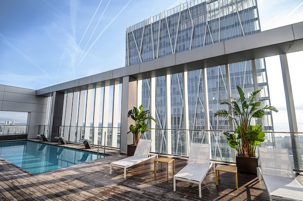 高層ビルの美しい街の景色を望む屋上のプール