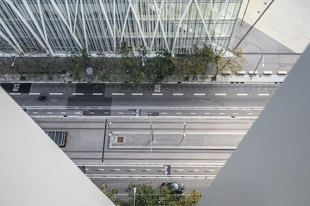 Оживленная городская улица с автомобилями и людьми, современными домами и небоскребами.