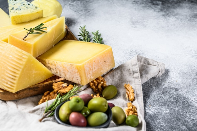 Сырная тарелка подается с виноградом, крекерами, оливками и орехами. ассорти вкусные закуски. пространство для текста