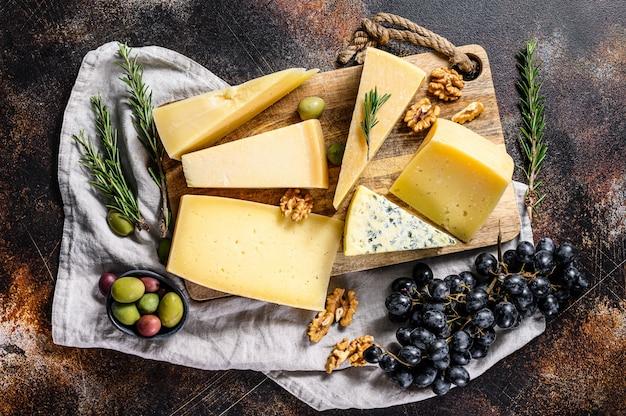 さまざまな種類のチーズ、オリーブ、ローズマリー。おいしいスナック盛り合わせ