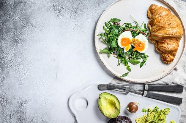 Завтрак, поздний завтрак с авокадо, рукколой, круассаном и яйцом. вид сверху