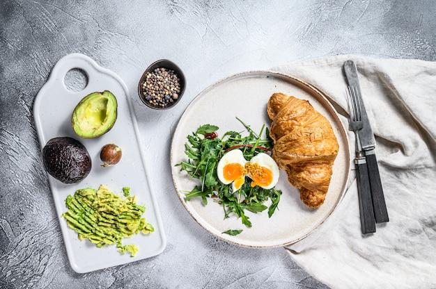 Салат с авокадо, рукколой, круассаном и яйцом. вид сверху