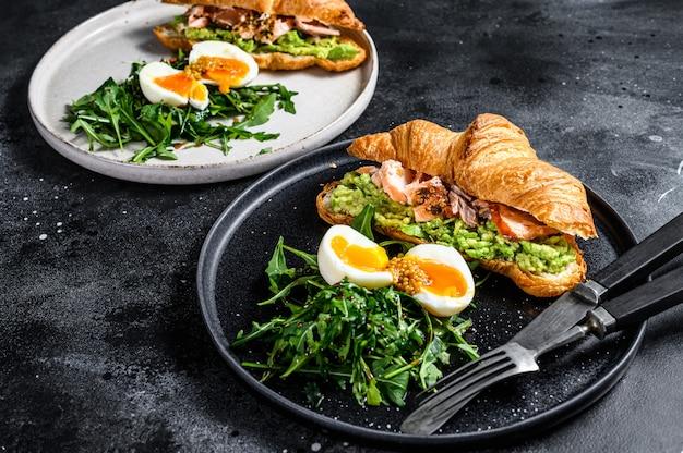 Завтрак, бранч круассан с лососем горячего копчения, авокадо. садовый зеленый салат с рукколой и яйцом. вид сверху