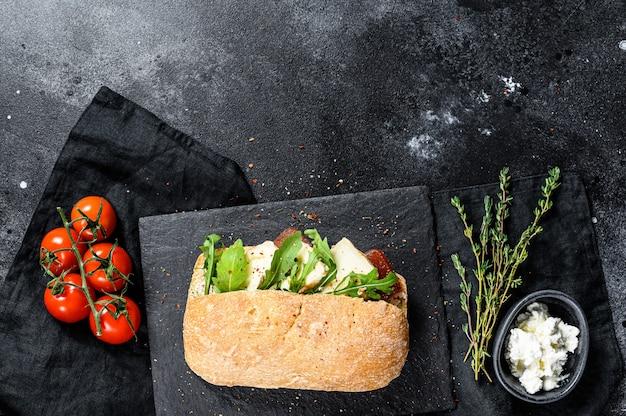 新鮮なカマンベールチーズ、梨のマーマレード、ルッコラのチャバタサンドイッチ。上面図。