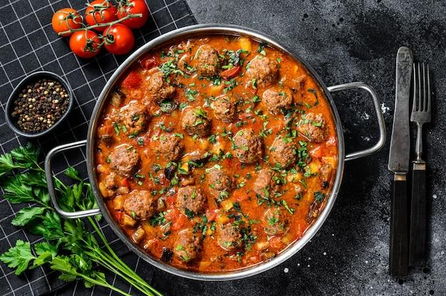 Свиные котлеты с томатным соусом и овощами на сковороде. вид сверху