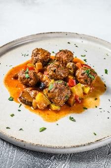Фрикадельки из говядины с томатным соусом и овощами на сковороде. вид сверху