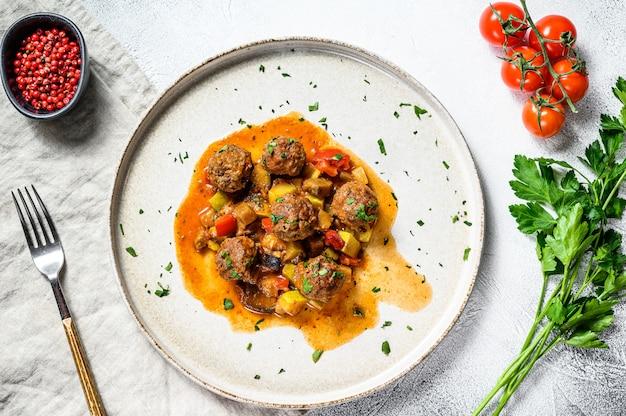 Вкусные фрикадельки из говяжьего фарша в томатном соусе, подаются на старой металлической сковороде. вид сверху