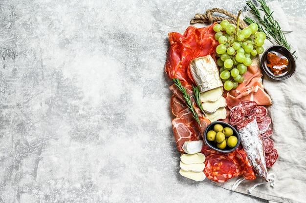 Итальянский антипасто, деревянная разделочная доска с ветчиной, ветчиной, пармой, козьим сыром и камамбером, оливками, виноградом. антипаста. вид сверху