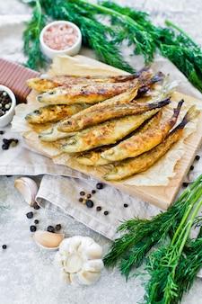 木のまな板、ディル、ピンクの塩、コショウ、ニンニクで揚げたワカサギ。
