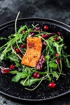 Салат из морепродуктов с лососем, рукколой, листьями салата и клюквой. вид сверху