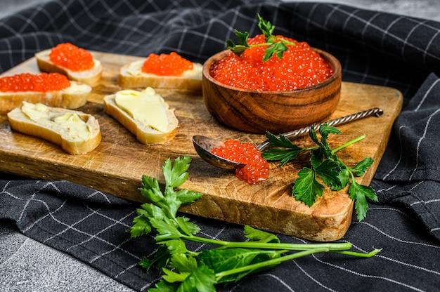 Красная икра в деревянной миске и бутерброды на разделочной доске. вид сверху.