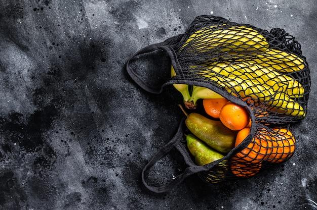 エコフレンドリーで再利用可能なショッピングストリングバッグ。果物が詰まっています。エコフレンドリー、プラスチックフリー。上面図。コピースペース