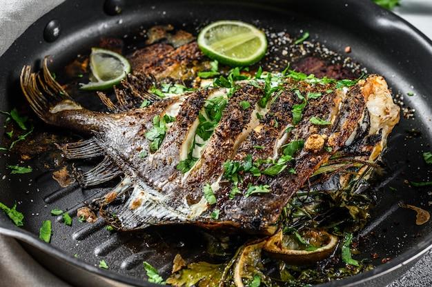 Жареная рыба дори с лаймом и петрушкой на сковороде. вегетарианская здоровая пища. вид сверху