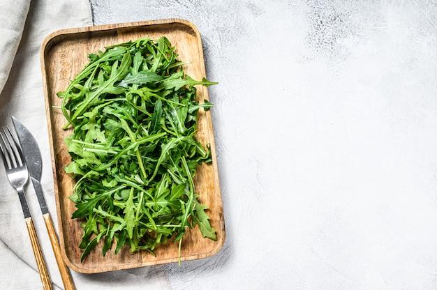 木製のボウルに新鮮なルッコラのサラダ。上面図。コピースペース