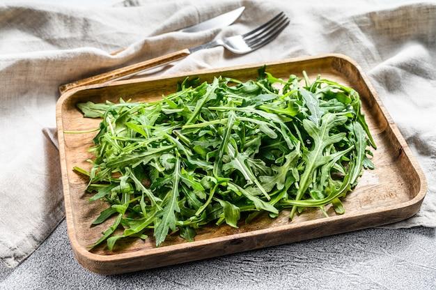 木製のボウルに新鮮なルッコラのサラダ。上面図