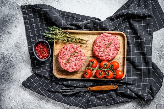 Сырые котлеты из гамбургеров, говяжий фарш. вид сверху
