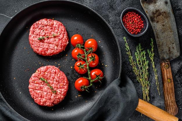 Сырой фарш из говяжьего мяса, котлеты в сковороде. вид сверху
